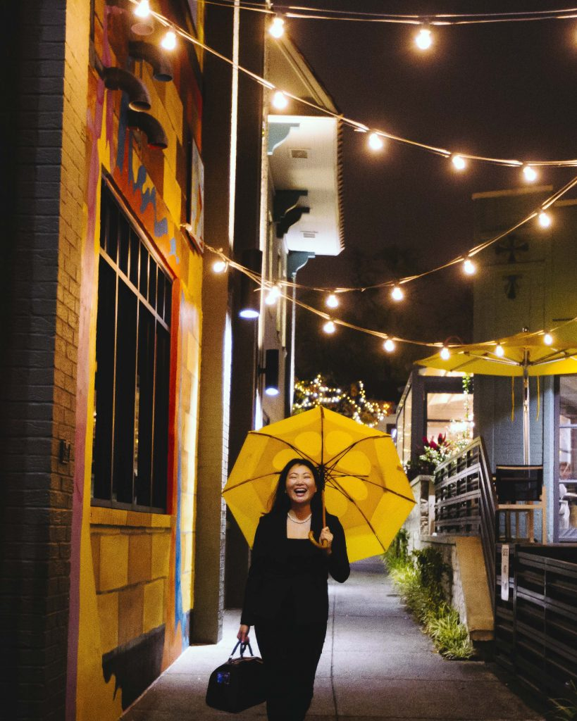 Wendy Marie holding a yellow umbrella, laughing, and walking through a festive alley