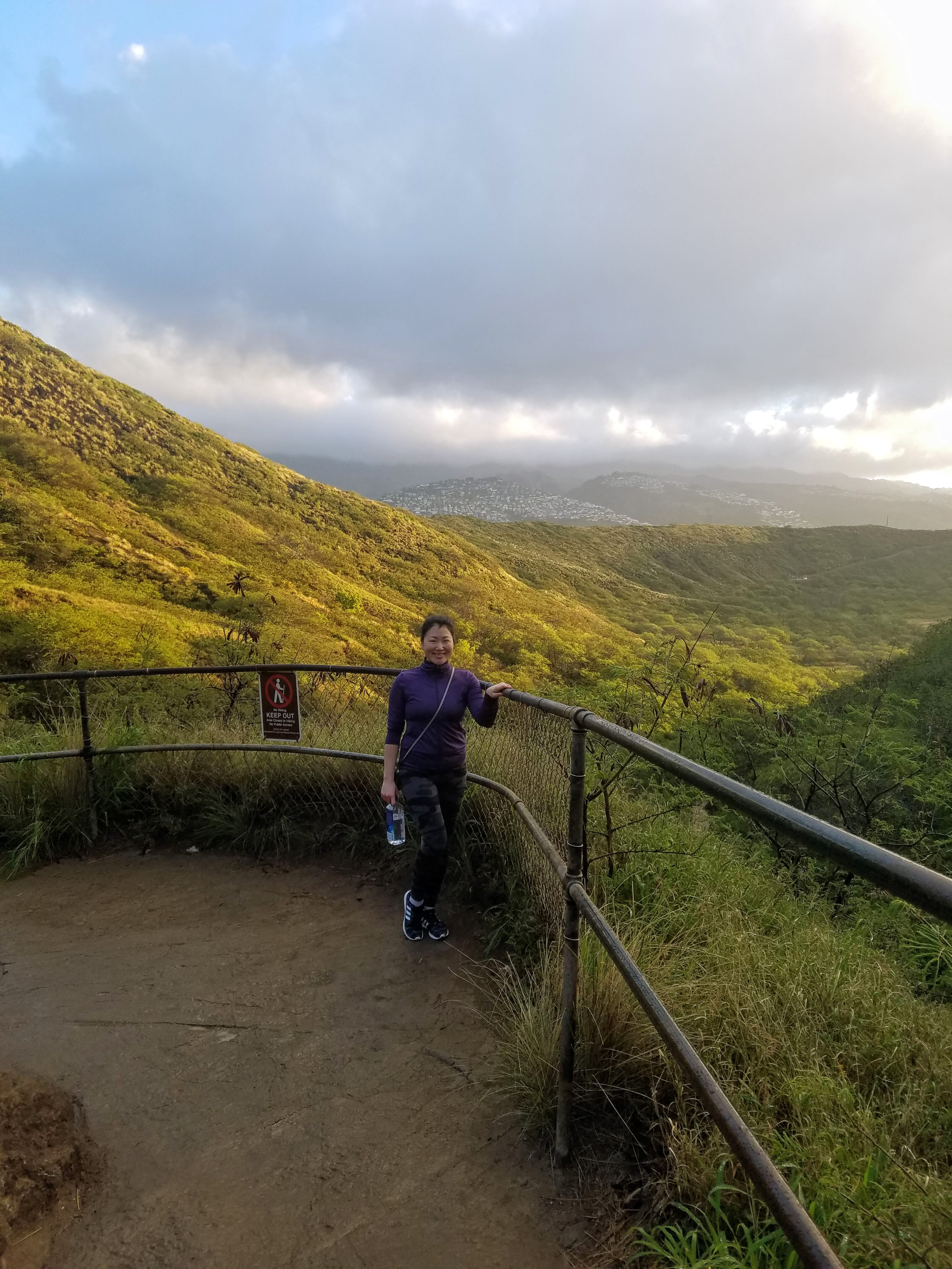 SunAh standing by the guard rails on the trail at Diamond Head crater. Behind her is verdant valleys.