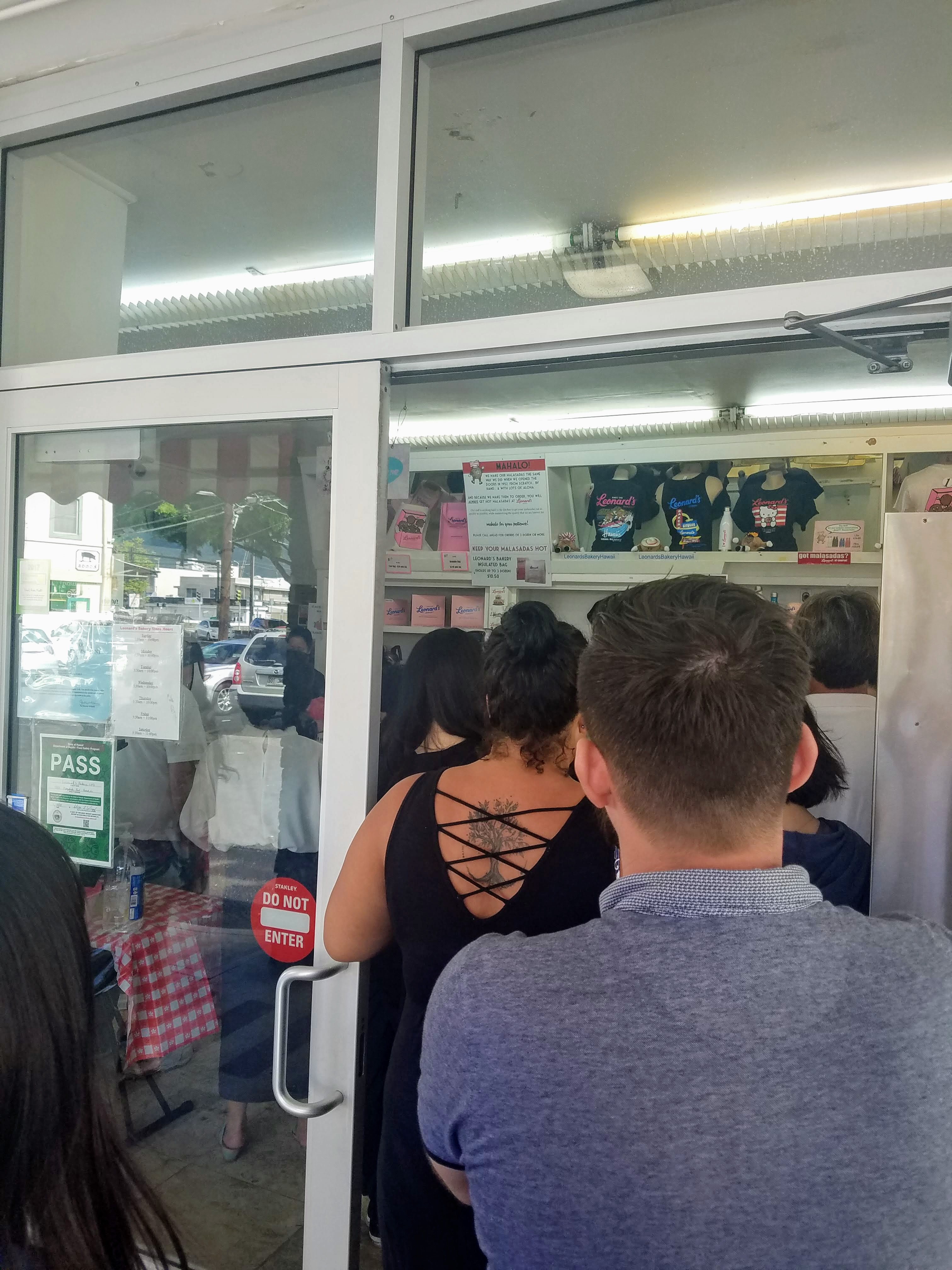 a line of people coming out of the door at Leonard's Bakery