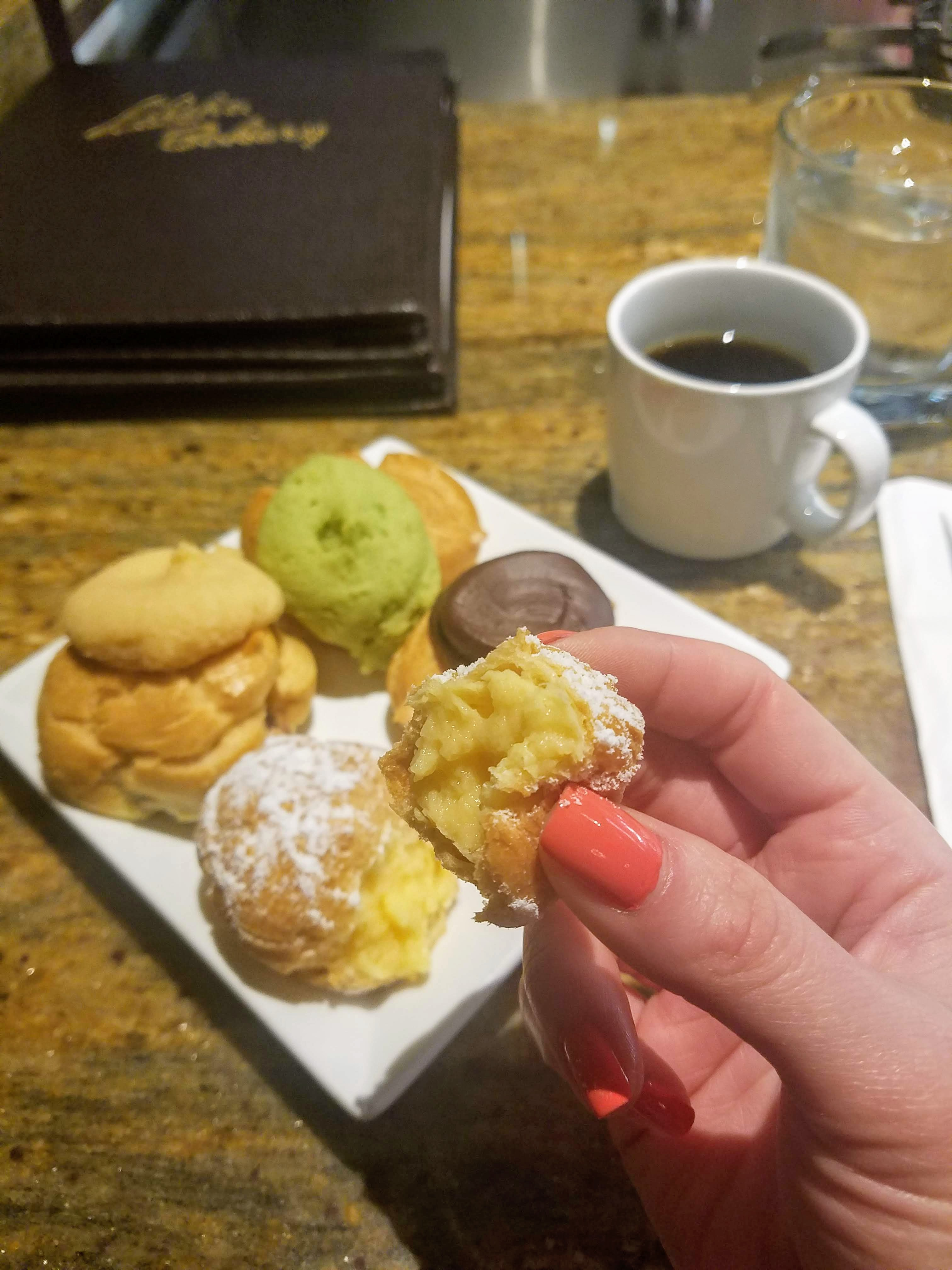 a piece of a cream puff filled with delicious cream. in the background is a plate of cream puffs of various flavors - green tea, chocolate, and coconut