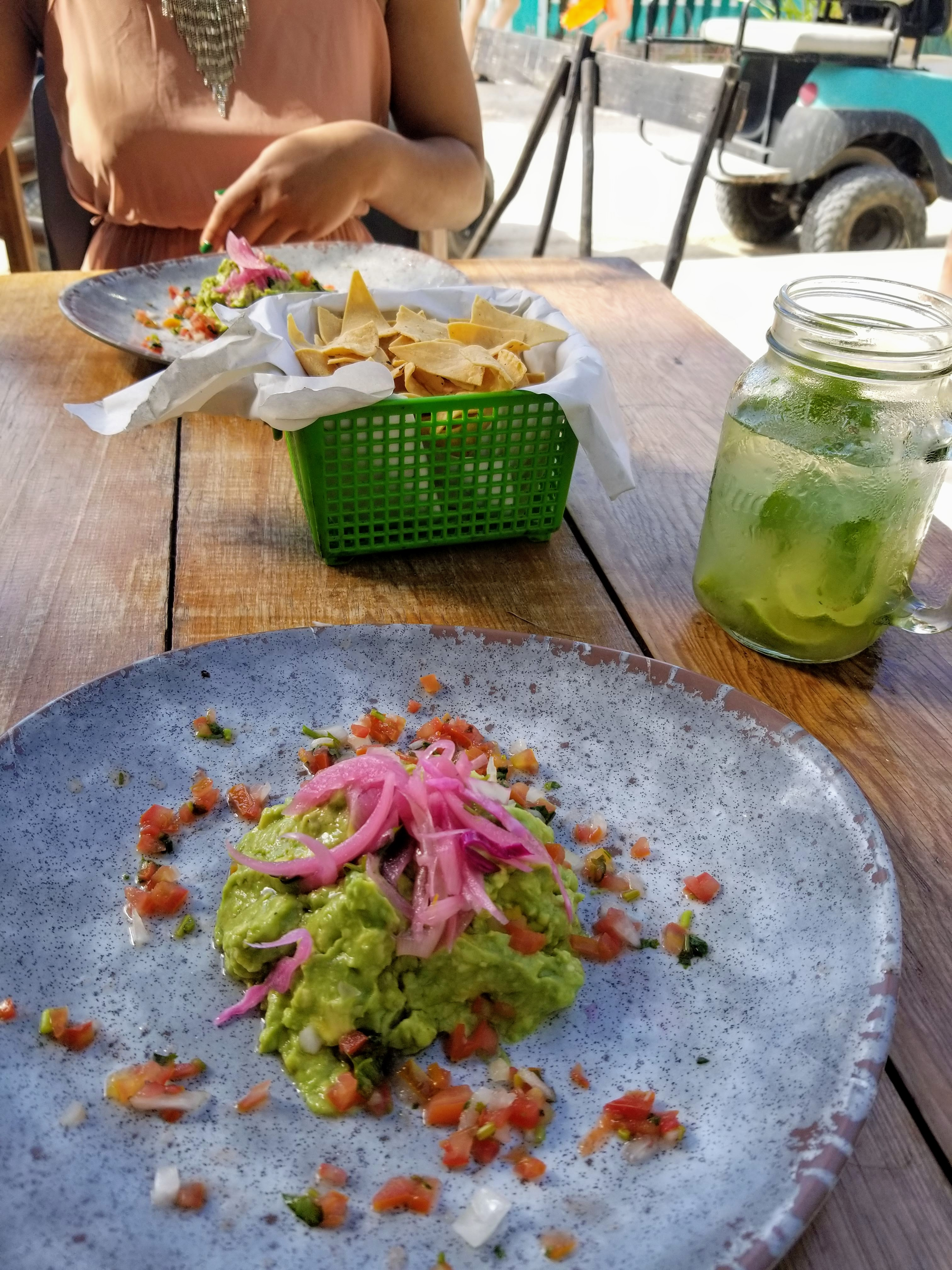 In the foreground is a large ceramic glazed plate with a beautiful mound of freshly made guacamole topped artistically with pickled onions. In the background is a basket of fresh made tortilla strips and a mojito.