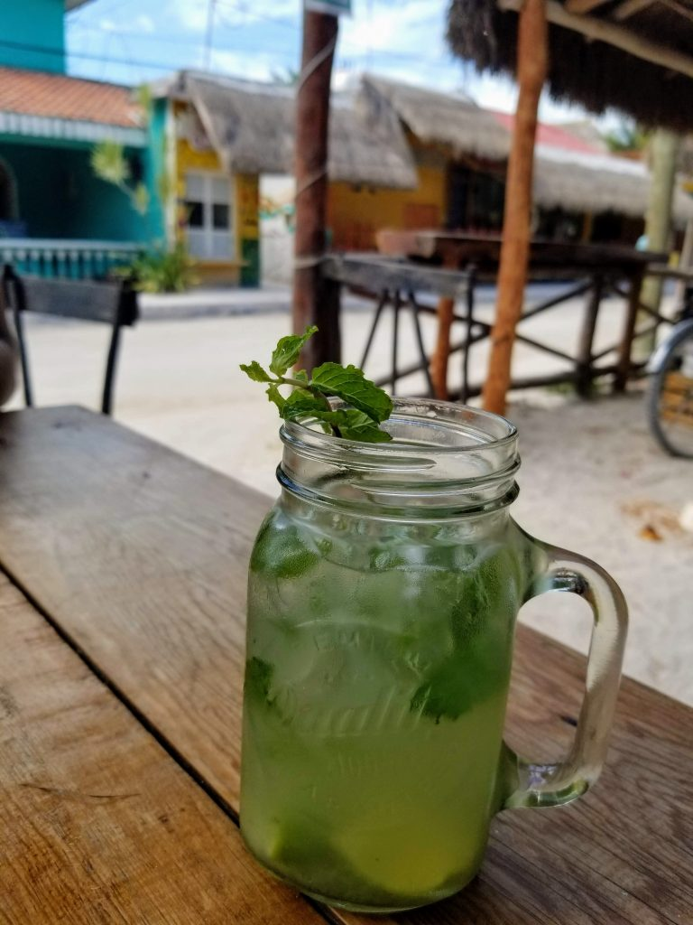 A mojito in a mason jar glass sits atop a dark brown plank table on the patio of a restaurant.