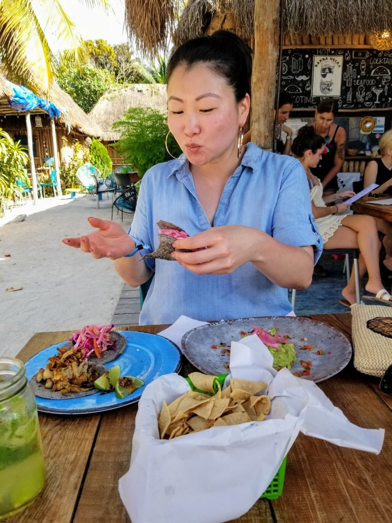 SunAh is clearly pleased with her tacos. She is holding a half eaten taco in one had. On the table in front of her is a half plate of guacamole and another plate with the two remaining tacos.