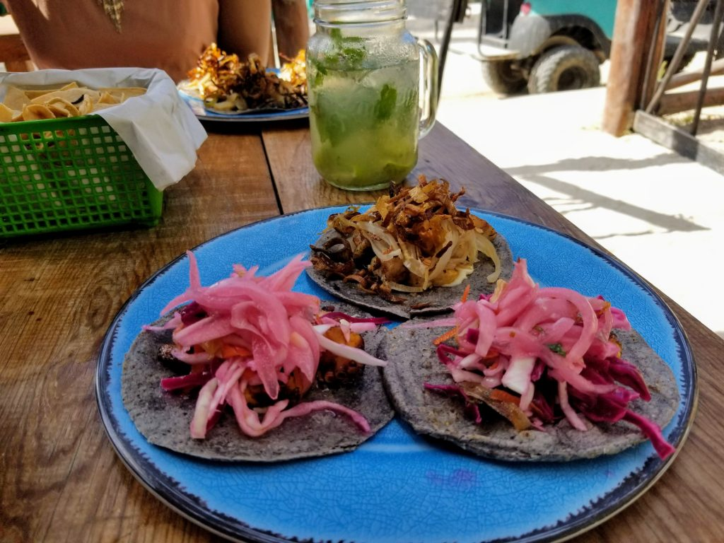 In the foreground is a bright cerulean ceramic glazed plate with three different tacos on blue corn tortillas. In the background is a mojito and another plate with three tacos.