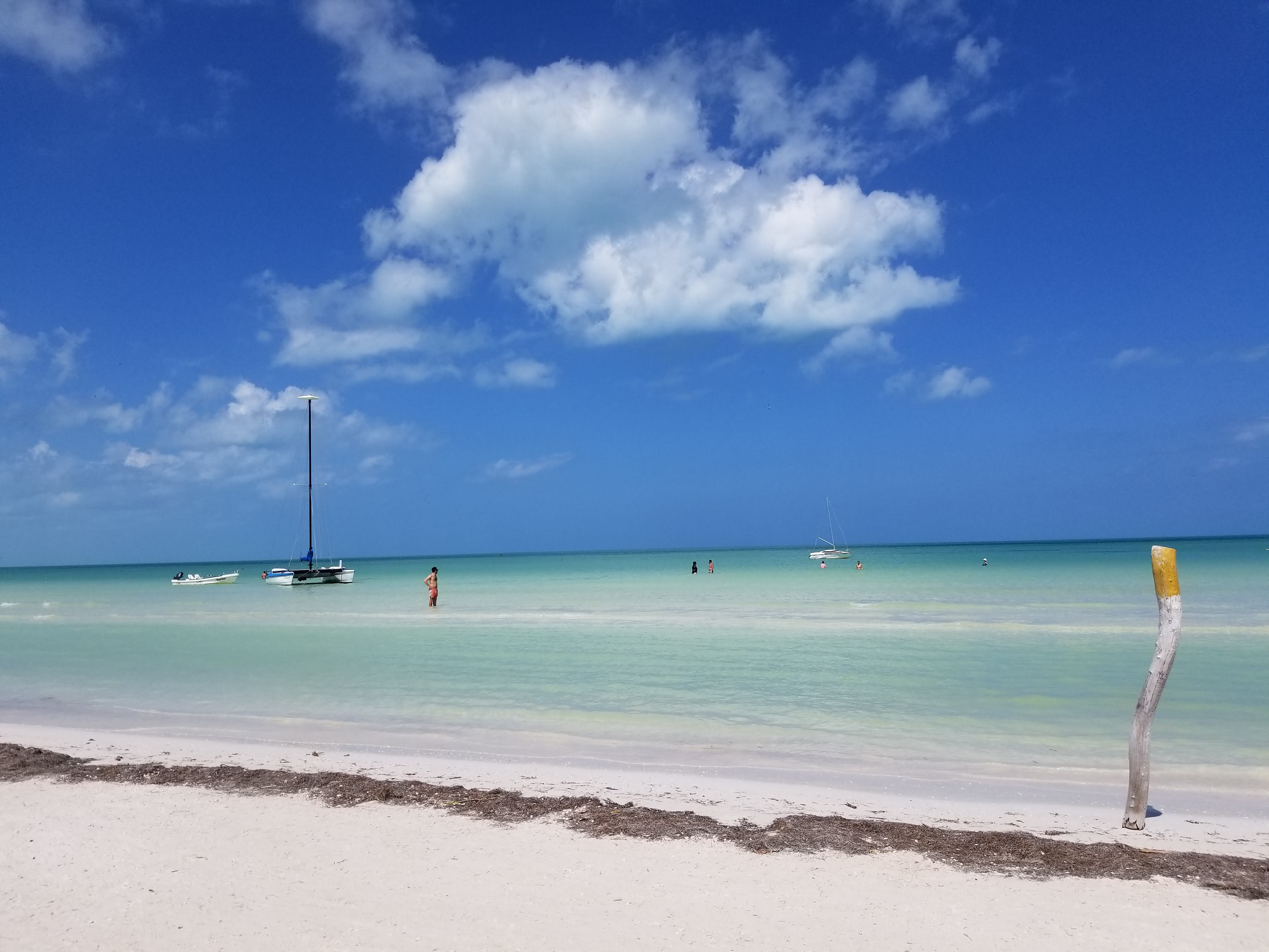 a beautiful beach view. the ocean goes all the way to the horizon. there are three small sailboats on the water. the sky is peppered with clouds.