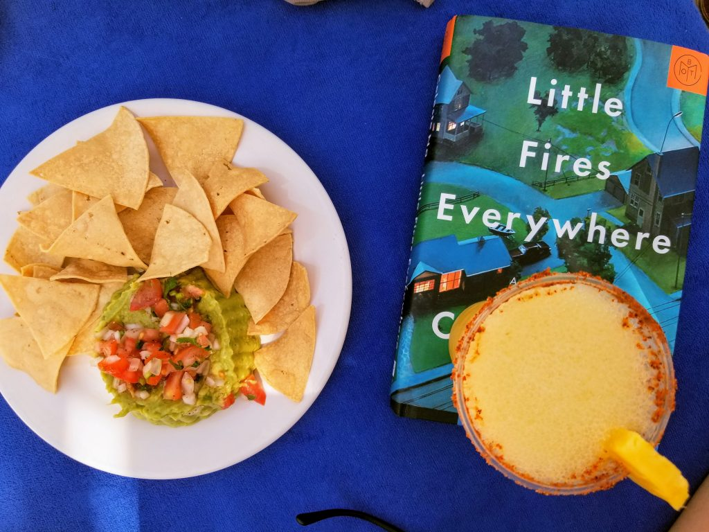 A plate of guacamole and chips is to the left of the book Little Fires Everywhere. On top of the book is a pineapple margarita.