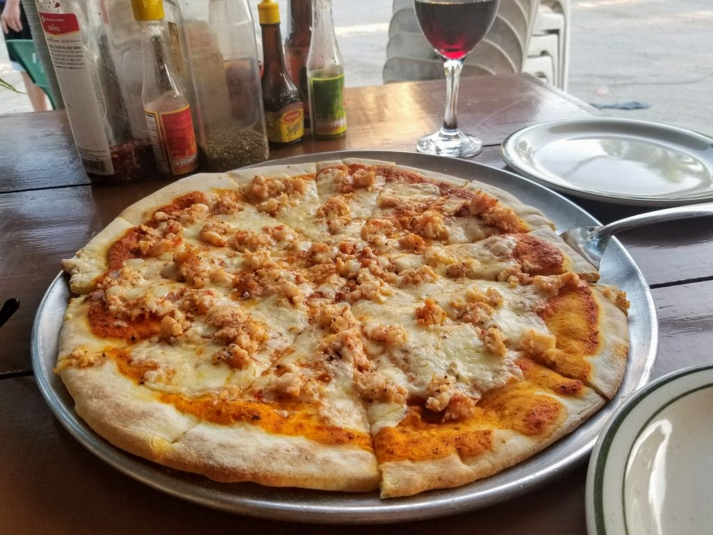 a large lobster pizza is in the foreground. in the background is a glass of red wine and an assortment of spices and hot sauces.