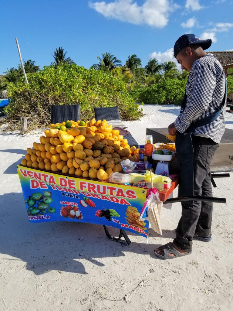 a man with his mango cart are on the beach. the cart is piled high with mangoes. the man is peeling a mango.