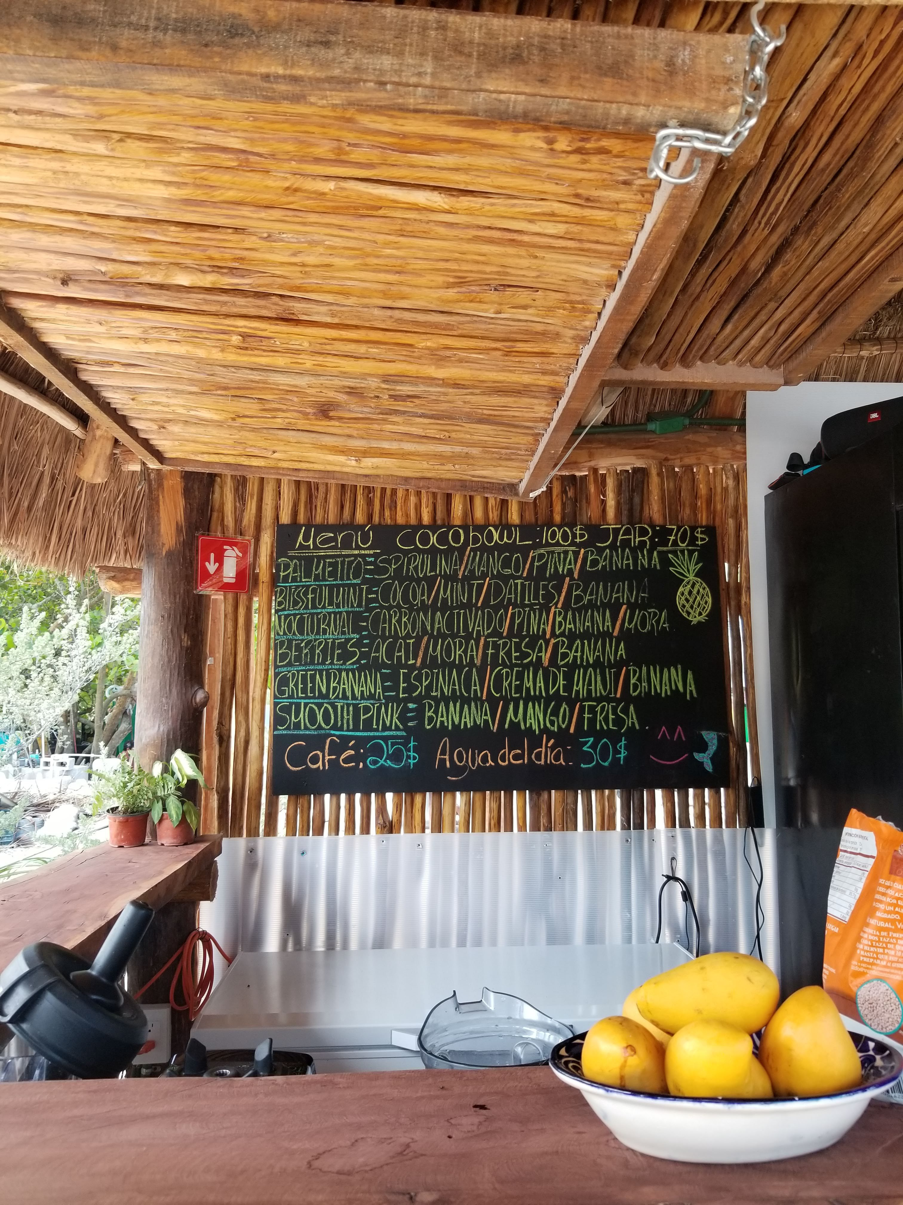 an open-air smoothie spot has a menu written in chalk. there are six different smoothies featured all with an assortment of island fruits like banana, mango, and coconut.